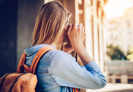 Une jeune touriste jeune et attrayante explore une nouvelle ville. La femme fait une photo sur une caméra rétro. À la recherche de nouvelles aventures. Banque d'images