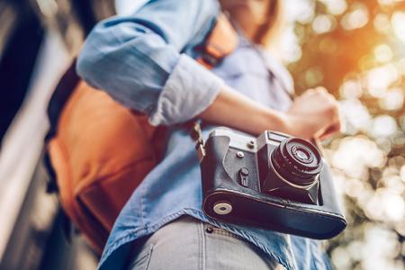 L'image recadrée d'une jeune touriste jeune et attrayante explore une nouvelle ville. Femme avec caméra rétro à la recherche de nouvelles aventures. Banque d'images