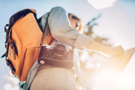 Attraktive junge weibliche Touristen erforscht neue Stadt. Frau mit Retro-Kamera und Karte in Händen ist auf der Suche nach neuen Abenteuern.