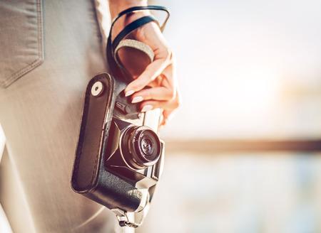 Freigestellte Bild von attraktiven jungen weiblichen Touristen erforscht neue Stadt. Frau mit Retro-Kamera auf der Suche nach neuen Abenteuern. Lizenzfreie Bilder