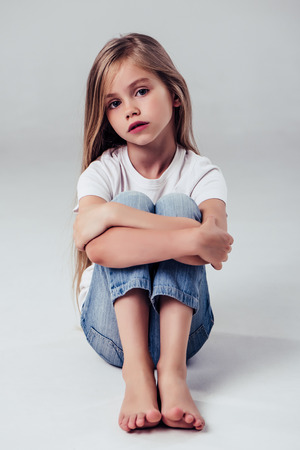 Little cute girl isolated. Charming blonde is posing on white background and looking at camera.