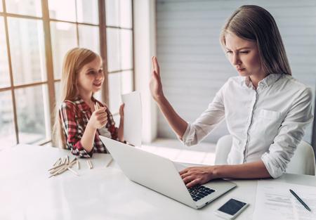 Estoy ocupado! Hermosa joven está trabajando en casa con su pequeña hija linda cerca. No tienes suficiente tiempo para el niño. Foto de archivo - 86079002