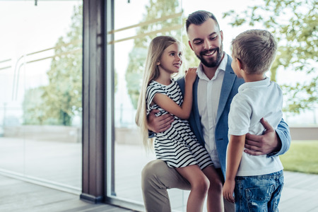 Dad arrives home from work, his little son and daughter are meeting him. Happy handsome man is kneeling, smiling and hugging his children. Imagens
