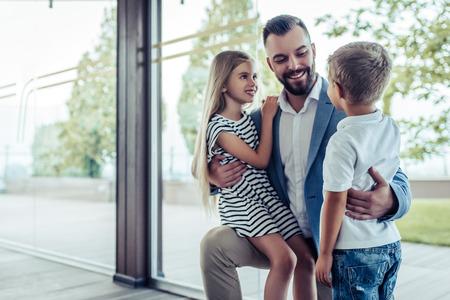 Vader komt thuis van zijn werk, zijn zoontje en dochter ontmoeten hem. De gelukkige knappe mens knielt, glimlacht en koestert zijn kinderen.