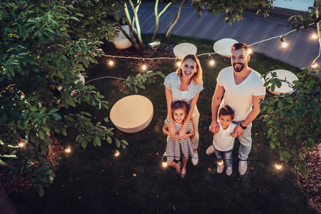 Top view of happy family is spending time together in park in the evening with garland of light bulbs. Parents with children are having fun and enjoying being together. Mom, dad, son and daughter outdoors. Stok Fotoğraf