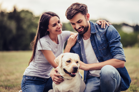 Beautiful romantic couple is having fun with their dog labrador retriever outdoors.