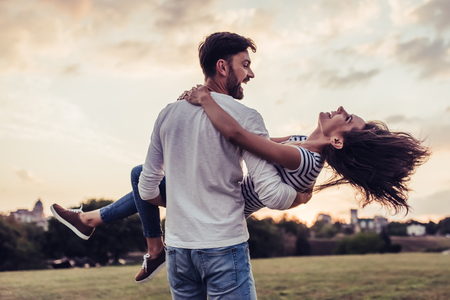 Beautiful romantic couple enjoying the company of each other outdoors. Handsome man picking his young woman un hands and circling. Stock Photo