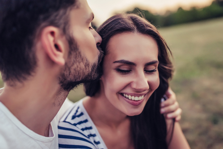 tenderly: Beautiful romantic couple enjoying the company of each other outdoors. Handsome man kisses tenderly his beautiful young woman in cheek.