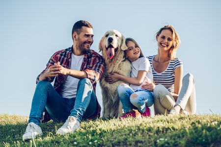Beautiful happy family is having fun with golden retriever outdoors. Mother, father and daughter are sitting with dog labrador on green grass in park.