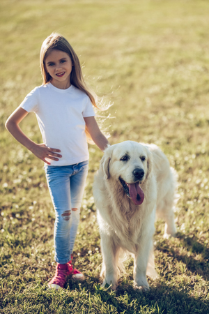 Little cute girl is having fun with golden retriever on a green grass. Charming cheerful girl is standing with dog labrador.