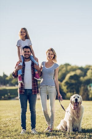 Full-length image of beautiful happy family is having fun with golden retriever outdoors. Mother, father and daughter are standing with dog labrador on green grass in park. 写真素材