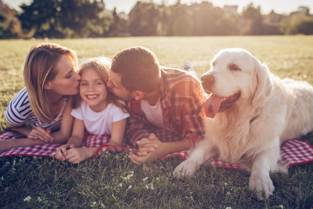 Beautiful happy family is having fun with golden retriever outdoors. Mother, father and daughter are lying with dog labrador on green grass in park. 写真素材