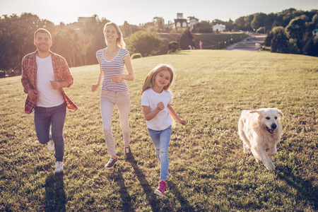 Beautiful happy family is having fun with golden retriever outdoors. Mother, father and daughter are running with dog labrador in park.