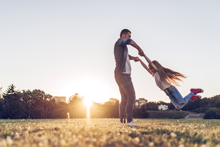 Handsome man is spending time with his little charming daughter outdoors. Dad and daughter are playing in park during the sunset.