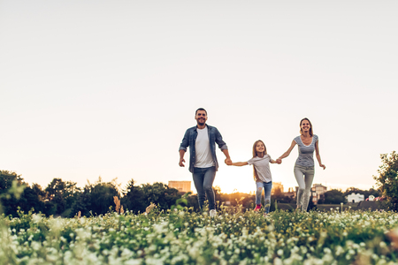 Happy family outdoors spending time together. Father, mother and daughter are having fun and running on a green floral grass during the sunset. Lizenzfreie Bilder