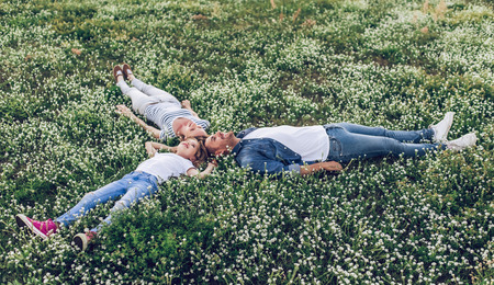 Happy family outdoors spending time together. Father, mother and daughter are having fun while lying on a green floral grass.