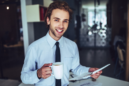 Young handsome businessman in light modern office. Smiling and looking at the camera with cup of coffee in hands.