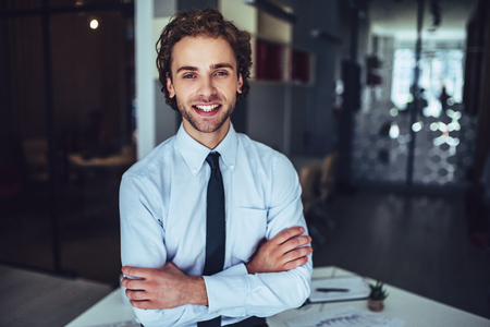 Young handsome businessman in light modern office. Smiling and looking at the camera.
