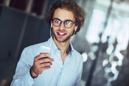 Young handsome businessman in light modern office. Listening to music using smart phone.