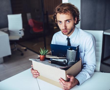 Jonge knappe zakenman in lichte moderne kantoor met kartonnen doos. Laatste dag op het werk. Boos kantoormedewerker wordt ontslagen.
