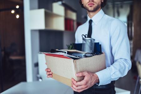 Junger hübscher Geschäftsmann im hellen modernen Büro mit Kartonkasten. Letzter Tag bei der Arbeit. Verärgerter Büroangestellter wird gefeuert. Standard-Bild