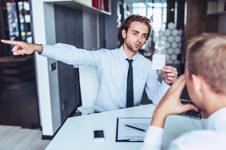 Young handsome businessman in light modern office. Director is firing worker.