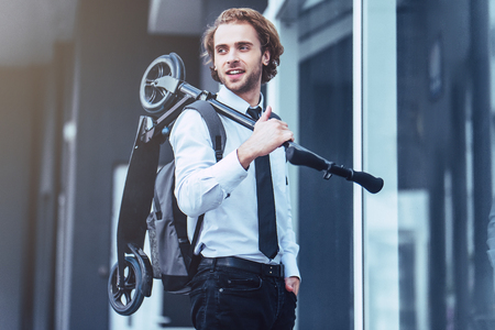 Young handsome businessman on street with kick scooter. Stockfoto