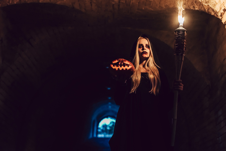 Happy Halloween! Portrait of black witch with scary makeup in black mantle is standing in dark cave with torch and flaming pumpkin in hands. Stock Photo
