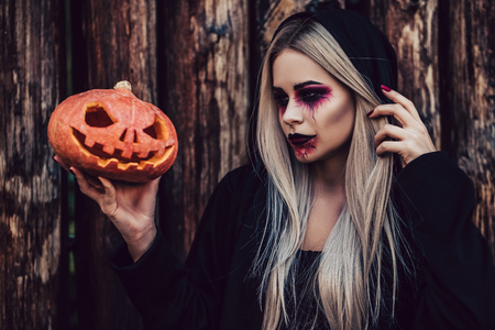 Happy Halloween! Portrait of black witch with scary makeup in black mantle on wooden background. Holding  pumpkin in hands