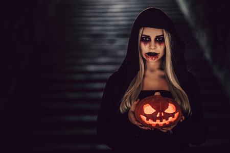 Happy Halloween! Portrait of black witch with scary makeup in black mantle. Holding  pumpkin in hands Stock Photo