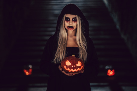 Happy Halloween! Portrait of black witch with scary makeup in black mantle. Holding pumpkin in hands