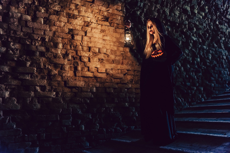 Happy Halloween! Full-length image of black witch with scary makeup in black mantle. Holding  pumpkin and lamp in hands Stock Photo