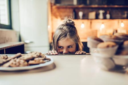 Urocza mała dziewczynka w kuchni patrzy spod stołu na słodycze. Gotowe do zjedzenia ciasteczek i ciastek.