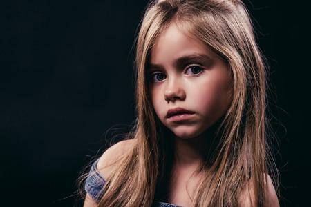 긴 머리를 가진 작은 귀여운 소녀의 초상화는 검은 배경에 포즈입니다. 격리 된 매력적인 금발입니다. 스톡 콘텐츠