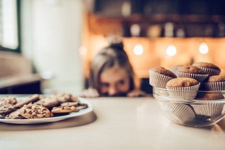 Charmant klein meisje op de keuken kijkt van onder de tafel op snoep. Klaar om wat koekjes en gebak te eten.