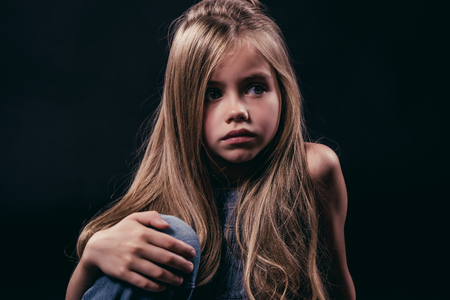 Little cute girl with long hair is sitting on black background. Charming blonde isolated.