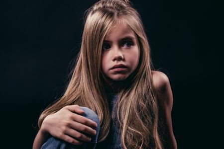 Weinig leuk meisje met lang haar zit op zwarte achtergrond. Charmante geïsoleerde blonde.