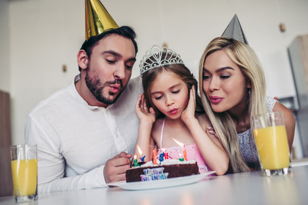 Happy family is celebrating little daughters Birthday. Mother, father and daughter on kitchen. Stock Photo