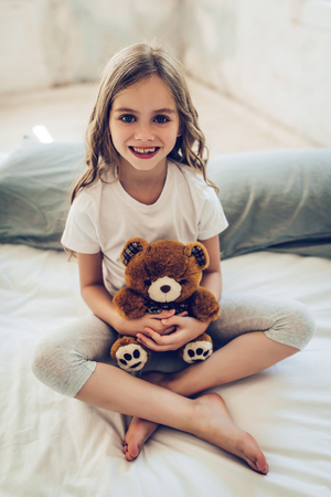 Cropped image of little cute girl is sitting on bed with plush toy in hands and smiling.