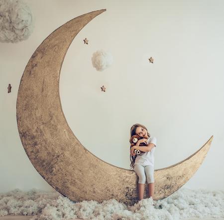 달콤한 꿈. 봉 제 장난감으로 귀여운 소녀 면화 구름과 별 인공 문에 앉아있다 스톡 콘텐츠
