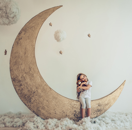 pijama: Sweet dreams. Little cute girl with plush toy is sitting on artificial Moon with cotton clouds and stars