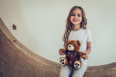 달콤한 꿈. 작은 귀여운 소녀 봉 제 장난감 인공 문에 앉아있다.