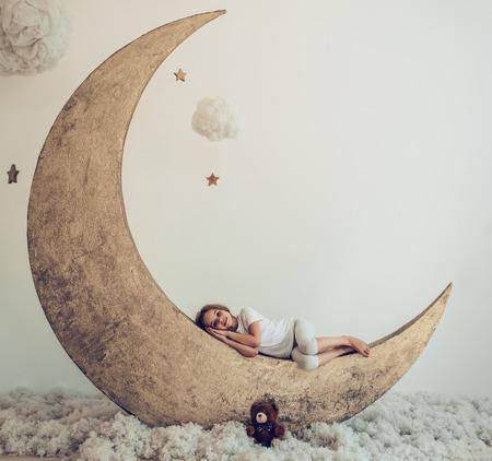 달콤한 꿈. 봉 제 장난감으로 귀여운 소녀 면화 구름과 개 인공 문에 누워있다
