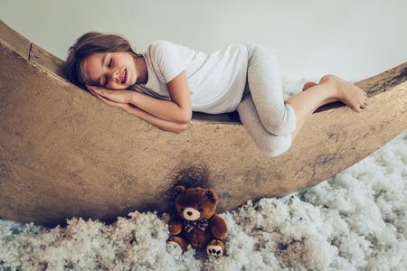 Dulces sueños. Linda niña con peluche está durmiendo en la luna artificial con nubes de algodón