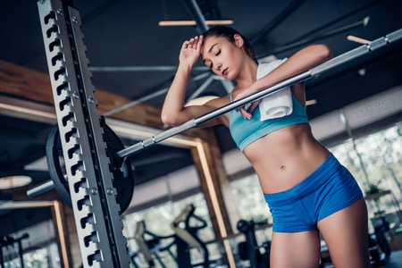 Sports woman with barbell. Taking break between repetitions.
