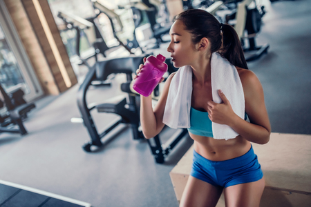 Sports woman in gym. Drinking water while sitting on jumping box