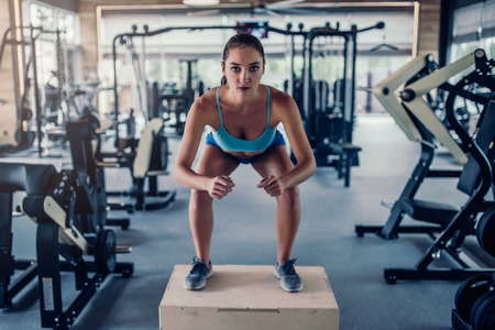 Sports woman with jumping box. Attractive girl is doing exercises with box in gym.