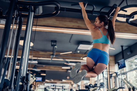 Sports woman in gym. Attractive girl is doing exercises for abs. Abdominal training.