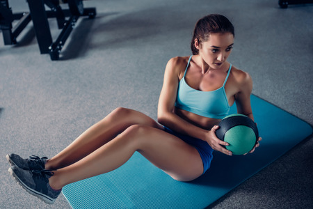 Sports woman in gym. Attractive girl is doing exercises for abs. Abdominal training with ball.