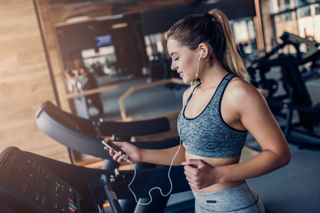 Attractive sports woman on running track is listening to music with mobile phone in hand using earphones.